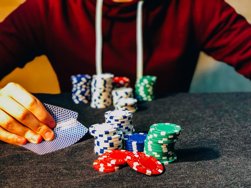 A set of poker chips in the table in front of player holding cards