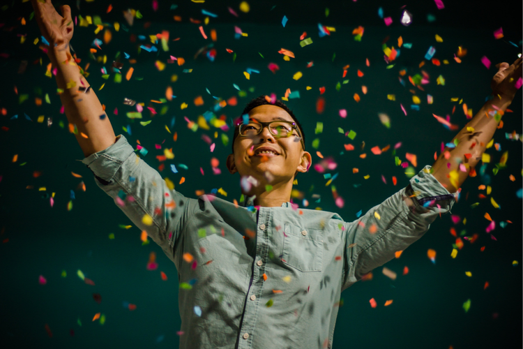 Man is surrounded by confetti flying through the air